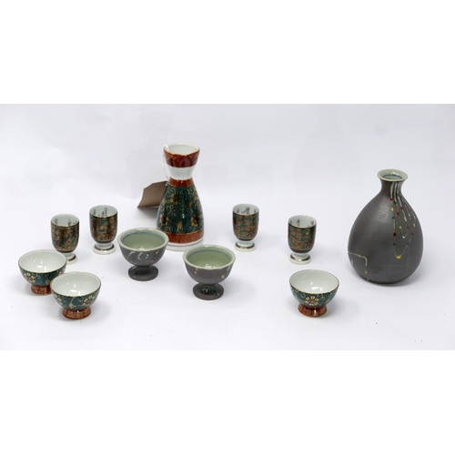 39 - Two Japanese sake jars and a collection of sake cups...