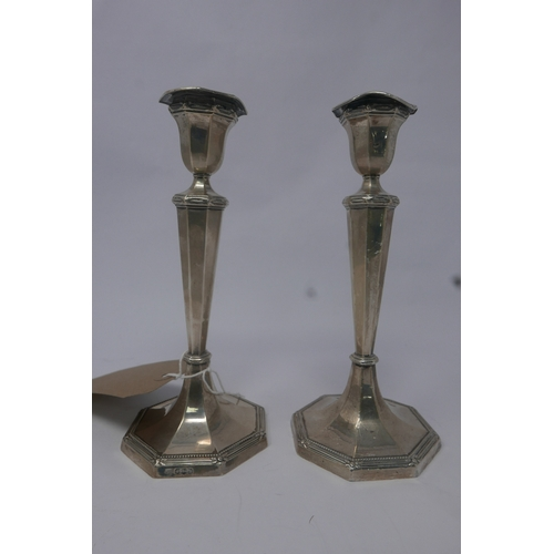 46 - A pair of filled silver candlesticks, raised on octagonal base, by Harrison Brothers & Howson (Georg...
