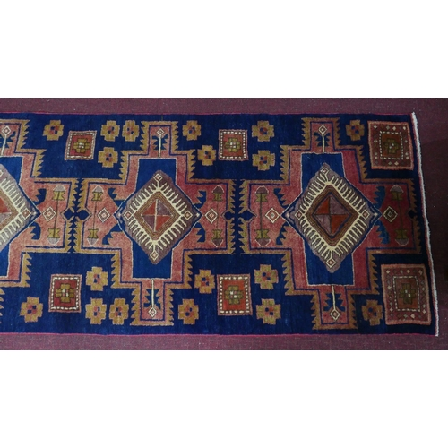 74 - A North West Persian Heriz runner, repeating stylised eagle motifs on a sapphire field, 282 x 89cm...