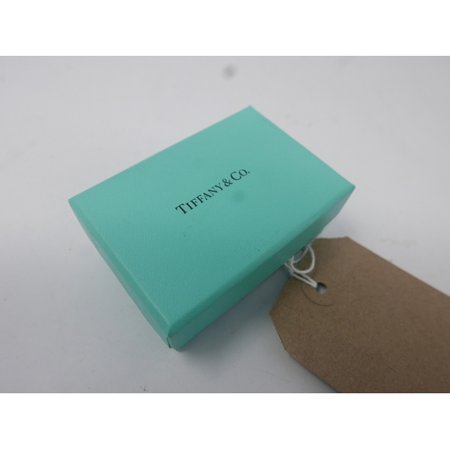 28 - A Tiffany & Co. silver key ring, marked 925, in Tiffany bag and box...
