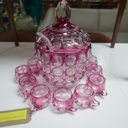 23 - A pink glass punch bowl and cover, H.35cm, with twelve matching cups, together with an associated gl...