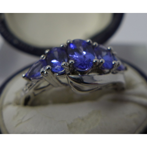 1222 - A boxed 14ct white gold tanzanite ring set with five graduated oval faceted natural tanzanite stones...