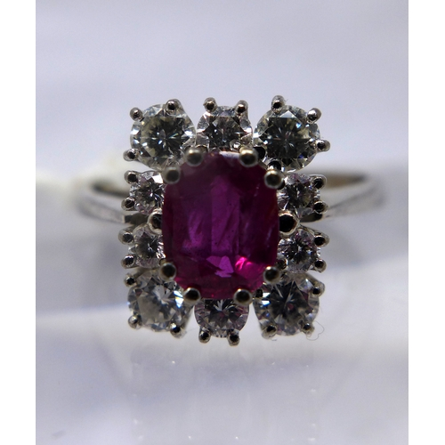 1030 - An 18ct white gold, natural ruby and diamond cluster ring, the central oval faceted natural ruby in ...