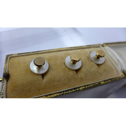 1054 - A set of three Victorian collar studs of 9ct rose gold and mother of pearl in original box, 12mm dia...