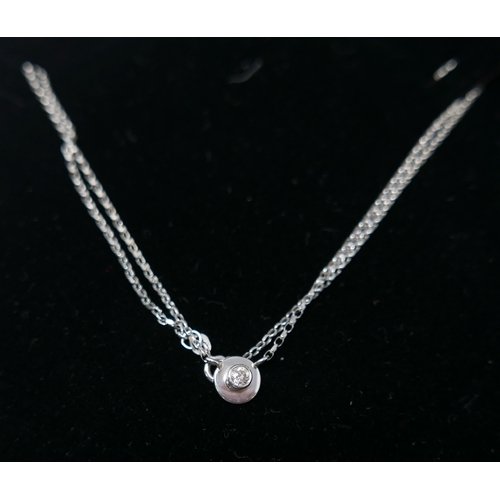 1055 - A boxed, 18ct white gold and diamond circular disc pendant (0.14 carats) on an 9ct white gold chain,...