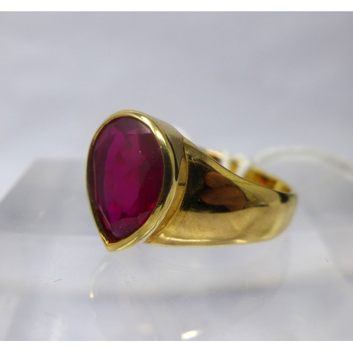 1060 - A 9ct yellow gold and ruby ring, centrally collet-set with a large, faceted, pear-drop ruby to wide ...