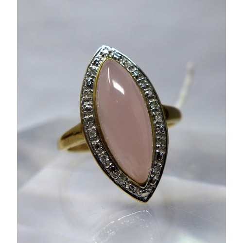 1064 - A 9ct yellow gold diamond and rose quartz ring, centrally set with a marquise-shaped rose quartz cab...