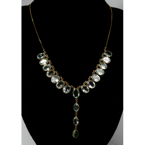 1051 - A 14ct yellow gold, drop necklace suspended with eighteen, faceted, oval, natural aquamarines, L: 48...