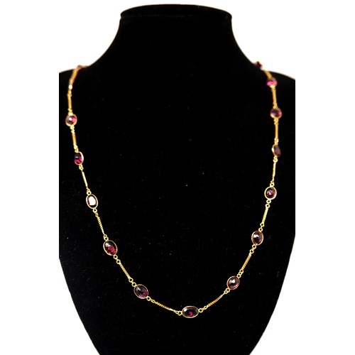 1111 - A 14ct yellow gold chain necklace interspaced with twenty-two, oval, natural faceted garnets, L: 62c...