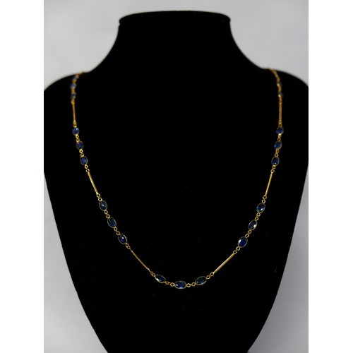 1075 - A 14ct yellow gold and sapphire chain necklace interspaced with thirty-three, oval, natural, faceted...