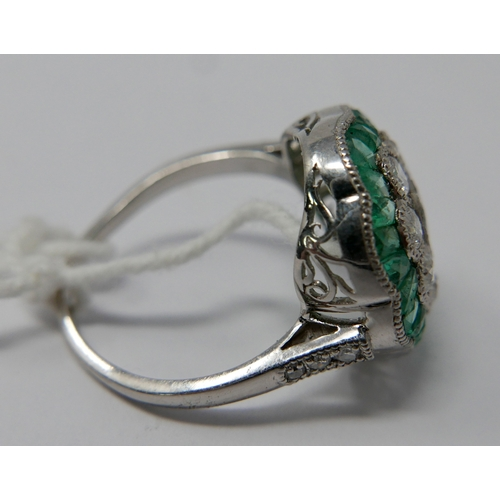 30 - A platinum, diamond, emerald and aquamarine cluster ring, centrally set with an oval aquamarine surr...