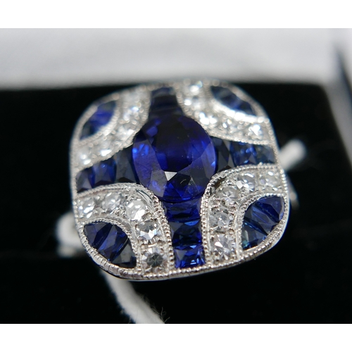 25 - A boxed platinum Art Deco style ring, with diamonds and sapphires set to the centre with an oval, fa...