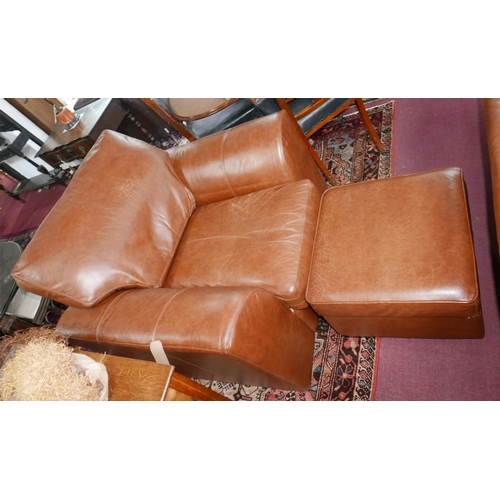 236 - A contemporary brown leather armchair and matching stool...