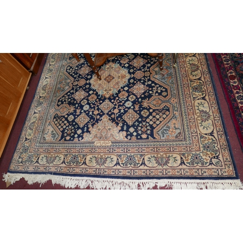 90 - A signed Nepalese carpet with geometric floral motifs on a blue ground, contained by floral border o...