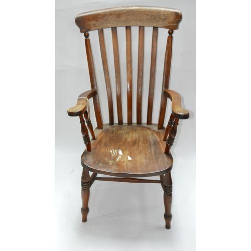 255 - An early 20th century oak Windsor armchair...
