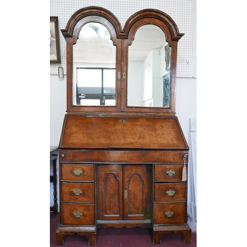 128 - An early 18th century walnut bureau bookcase, the two arched mirrored doors enclosing drawers and sh...