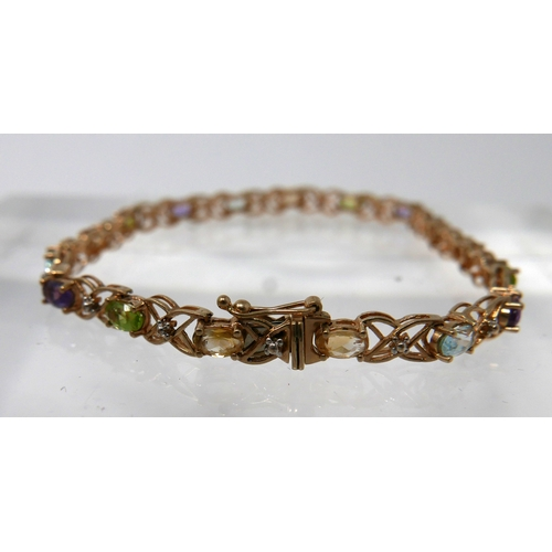1119 - A 9ct yellow gold tennis bracelet alternately set with faceted citrines, peridots, amethysts, aquama...