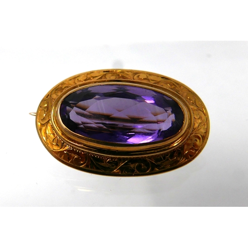 1036 - An 18ct yellow gold, Victorian, oval amethyst brooch with engraved scroll border, 1.7 x 2.5cm, 5.2g....