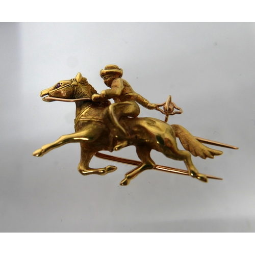1027 - An 18ct yellow gold horse and rider brooch with ruby eye to horse, 2.5 x 4cm, 9.1g...