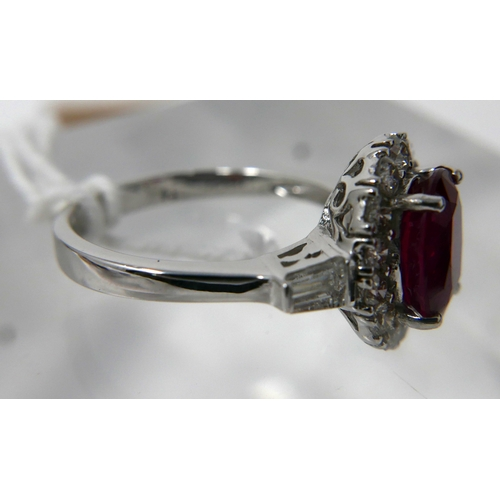 1039 - An 18ct white gold, ruby and diamond cluster ring, centrally set with an oval faceted ruby surrounde...