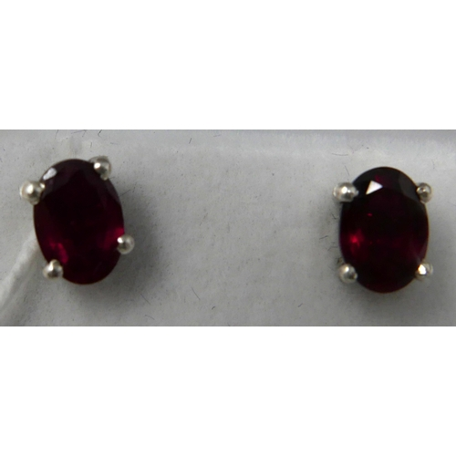 1157 - A boxed pair of sterling silver and ruby stud earrings, each earring composed of an oval, faceted ru...