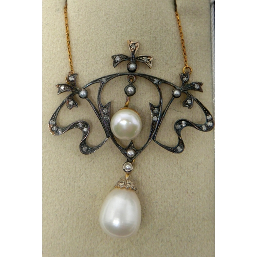 1066 - A boxed yellow gold necklace, the whiplash frame set with diamonds and small pearls suspended by two...