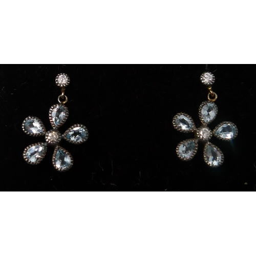 1052 - A boxed pair of yellow gold, diamond and faceted blue topaz flower-head earrings, L; 1.5cm, 2.5g....