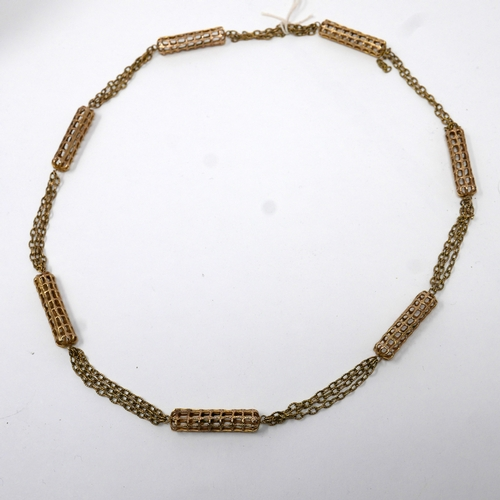 1044 - A 9ct yellow gold long chain necklace composed of seven pierced cylindrical panels  to three strand ...