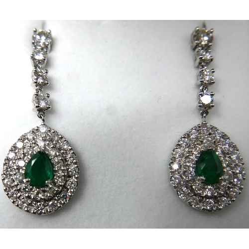 1008 - A boxed pair of 18ct white gold emerald and diamond cluster drop earrings, each earring suspended by...