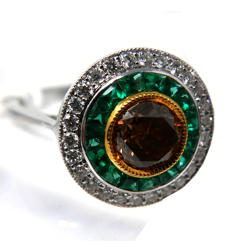1155 - An Art Deco style, 18ct white gold emerald and diamond target style ring, centrally set with a round...