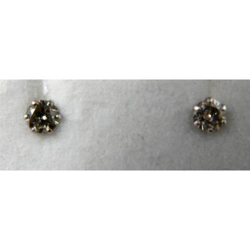 1127 - A boxed pair of platinum and brilliant cut diamond stud earrings (0.30 carats total)...