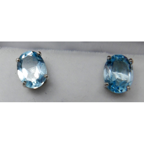 1147 - A boxed pair of sterling silver and oval, blue topaz stud earrings, 8 x 6mm, 1.6g....