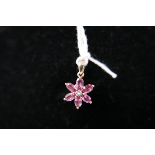 1098 - A 9ct yellow gold pendant composed of a flower-head set with 6 pink tourmaline petals and diamond st...