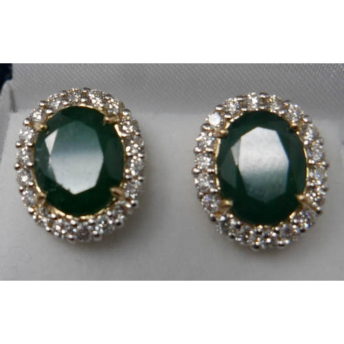 1085 - A boxed pair of 18ct yellow gold, emerald and diamond cluster stud earrings, each earring composed o...