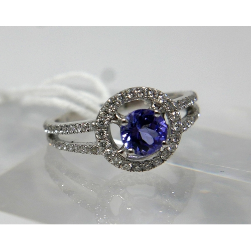 1159 - An 18ct white gold and tanzanite ring, composed of a central, circular facteted, tanzanite to a halo...