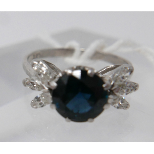 1056 - An 18ct white gold, sapphire and diamond ring, the round, faceted sapphire in 8-claw mount flanked b...