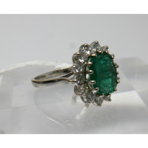 1004 - An 18ct white gold, emerald and diamond cluster ring, centrally set with a large, oval faceted emera...