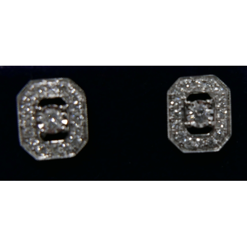 1042 - A pair of 18ct white gold and diamond stud earrings (0.50 carats), each earring set with a central r...