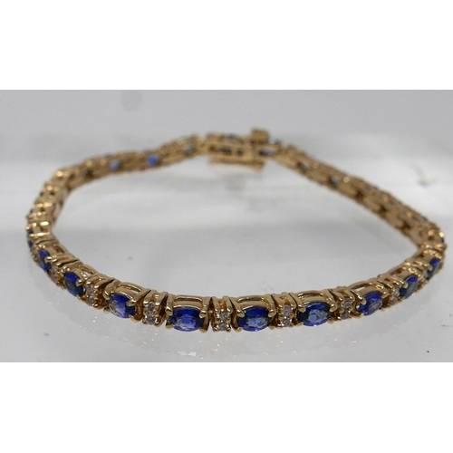 1017 - A 14ct yellow gold diamond and tanzanite tennis bracelet set with alternating stones of 50 diamonds ...