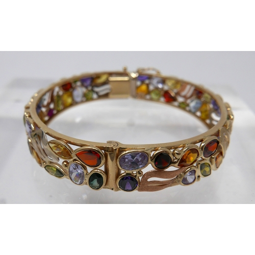 1070 - A yellow gold bangle studded with gemstones and rose gold accents, Dia: 6.5cm, 29g. (-sapphire, garn...