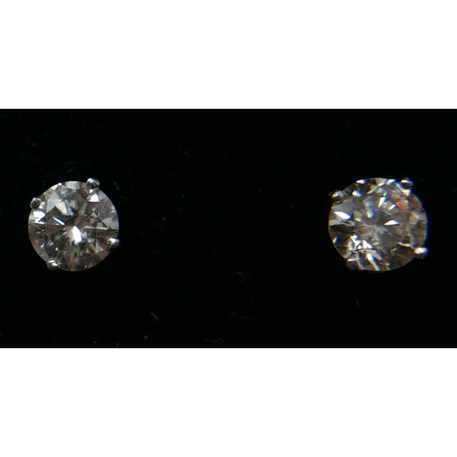 1100 - A pair of 14ct white gold, brilliant-cut diamond solitaire stud earrings (0.86 carats), 1g....