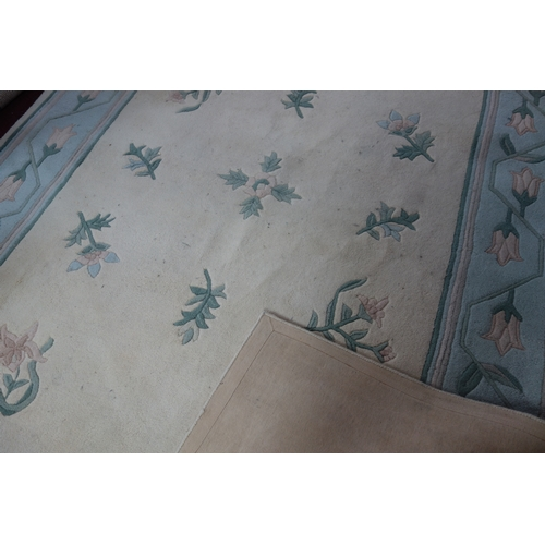 99 - A large woolen carpet with floral design on a cream ground, 313 x 230cm...