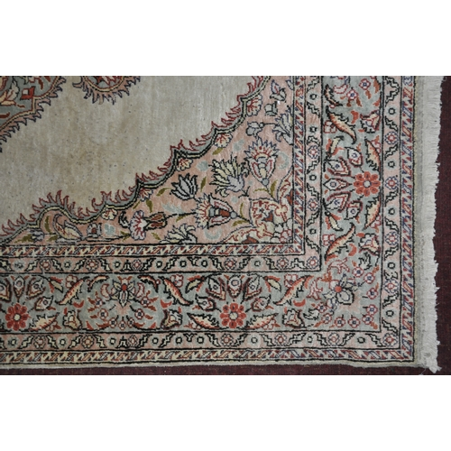 110 - A 20th century part silk Hereke rug, with floral medallion on a cream ground, contained by floral bo...