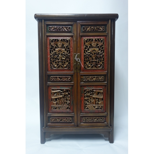 111 - A Chinese hardwood side cabinet with two doors having carved gilt wood and lacquered panels, H.100 W...