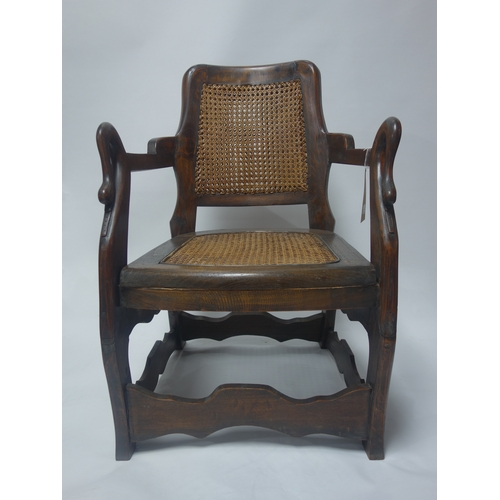 200 - A south east Asian teak chair with cane seat and backrest and swan neck handles...