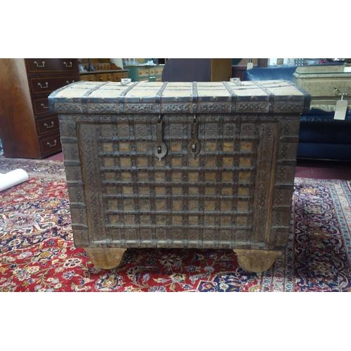 202 - A 19th century Indonesian iron bound teak trunk raised on wooden wheels, H.81 W.95 D.64cm...