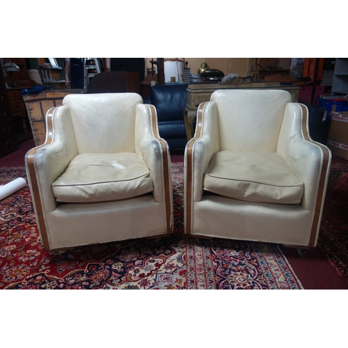 231 - A pair of Art Deco cream leather and walnut armchairs...