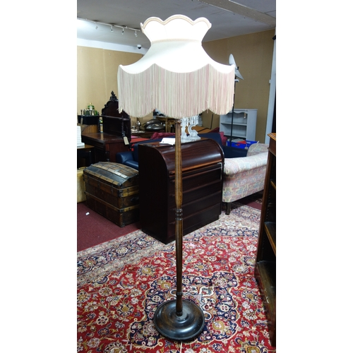 284 - A mahogany standard lamp with pink shade...