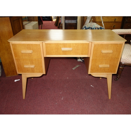 346 - A mid 20th century light oak desk, with five drawers, raised on splayed tapered legs, H.75 W.110 D.4...