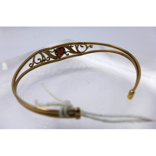 1225 - A 9ct yellow gold garnet bangle centrally set with a garnet cabochon flanked by floral arabesques, d...